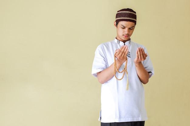 Junger asiatischer muslimischer mann, der betet, während rosenkranzperlen mit kopienraum halten
