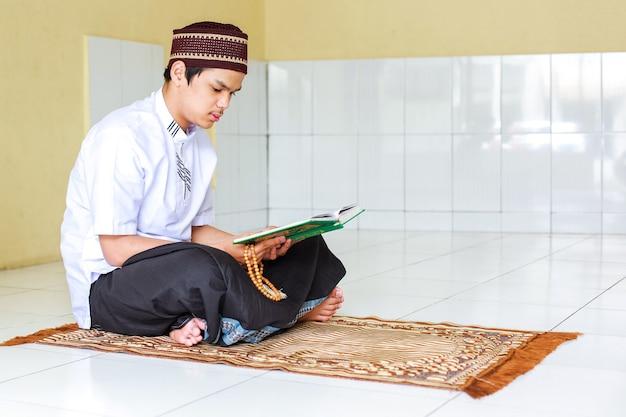 Junger asiatischer muslimischer mann, der gebetsperlen hält und das heilige buch alquran auf der gebetsmatte liest