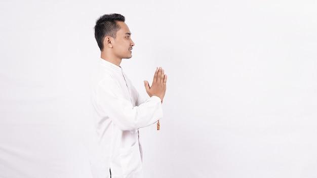 Junger asiatischer muslimischer mann mit begrüßung und begrüßungsgeste im ramadhan