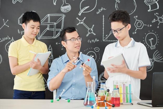 Junger asiatischer naturwissenschaftslehrer, der neugierigen schulkindern plastikmodell des chemischen moleküls zeigt, wenn sie notizen in heften machen