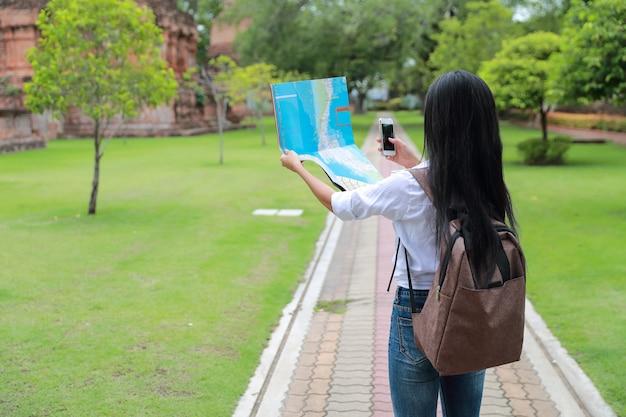 Junger asiatischer reisender, der handy verwendet und karte im tempel beim reisen während der feiertagsferien hält