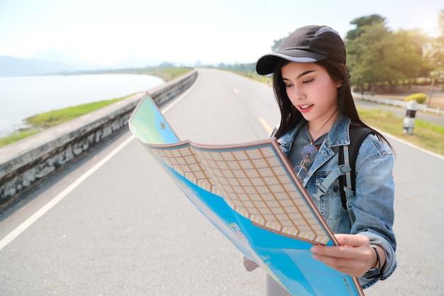 Junger asiatischer reisender, der richtung auf standortkarte beim reisen während der feiertagsferien sucht
