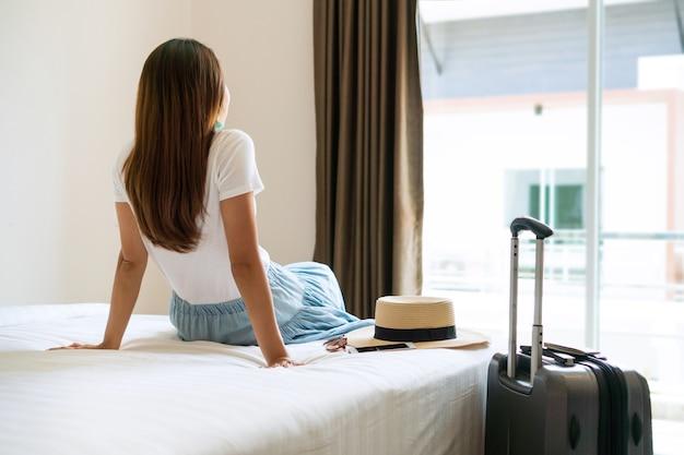 Junger asiatischer reisender im weißen t-shirt entspannend, der durch ein fenster im hotelzimmer nach dem einchecken schaut