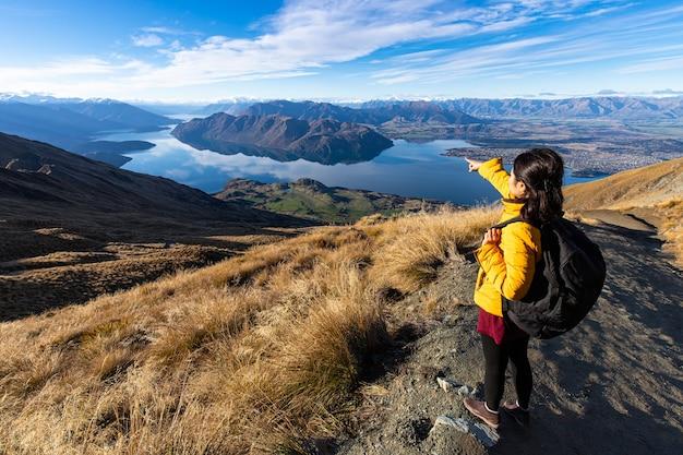 Junger asiatischer reisender rucksack, der auf roys peak track, wanaka, südinsel, neuseeland wandert