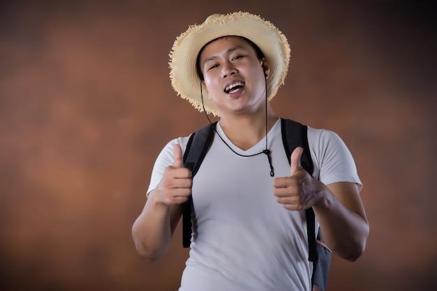 Junger asiatischer reisender wanderer mit tasche und hut