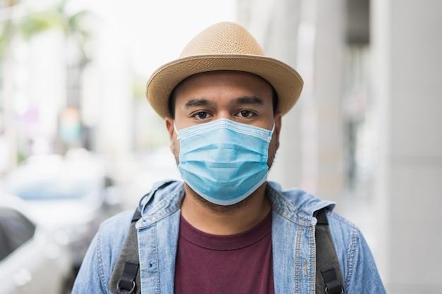 Junger asiatischer rucksacktourist, der in stadtstadt trägt gesichtsmaske reist.