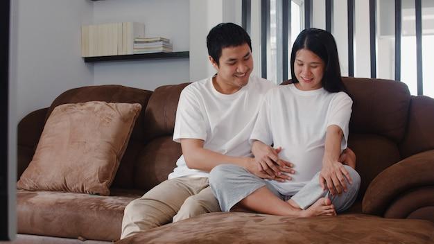 Junger asiatischer schwangerer paarmann berühren seinen fraubauch, der mit seinem kind spricht. die mutter und vati, die glücklich lächeln friedlich sich fühlen, während mach s gut baby, die schwangerschaft, die zu hause auf sofa im wohnzimmer liegt.