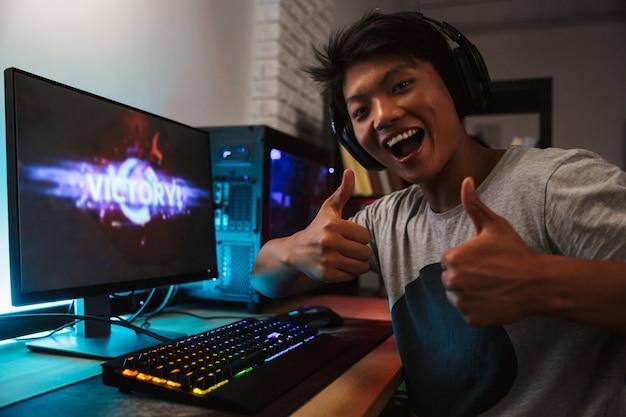Junger asiatischer spielerjunge freut sich über den sieg, während er videospiele am computer im dunklen raum spielt, kopfhörer trägt und bunte tastatur von hinten beleuchtet