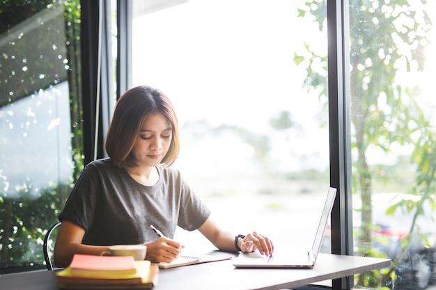 Junger asiatischer student, der auf notizbuch im café schreibt.
