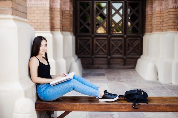 Junger asiatischer student, der ein buch liest, das auf bank am universitätscampus sitzt