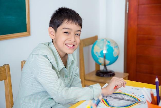Junger asiatischer student, der im klassenzimmer sitzt und an der kamera lächelt