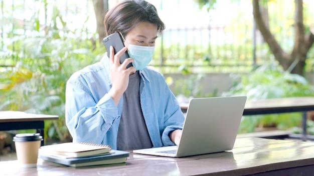Junger asiatischer student, der schutzmaske trägt, telefoniert und mit laptop-computer arbeitet