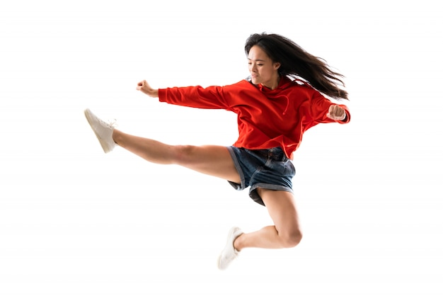 Junger asiatischer tänzer über getrennter weißer wand