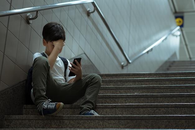 Junger asiatischer teenager, der an der treppe sitzt und sein gesicht mit der hand bedeckt