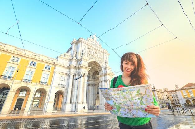 Junger asiatischer tourist, der die karte und das lächeln beim reisen in lissabon, portugal hält