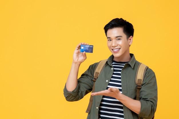 Junger asiatischer touristenmann, der kreditkarte hält