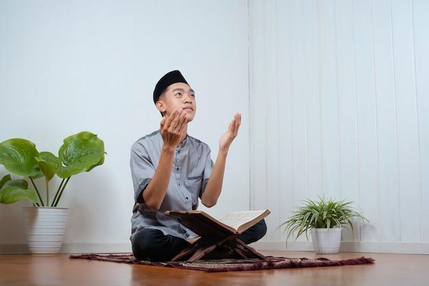 Junger asiatischer treuer muslimischer mann betet auf dem gebetsteppich mit dem koran auf ramadan kareem zu hause