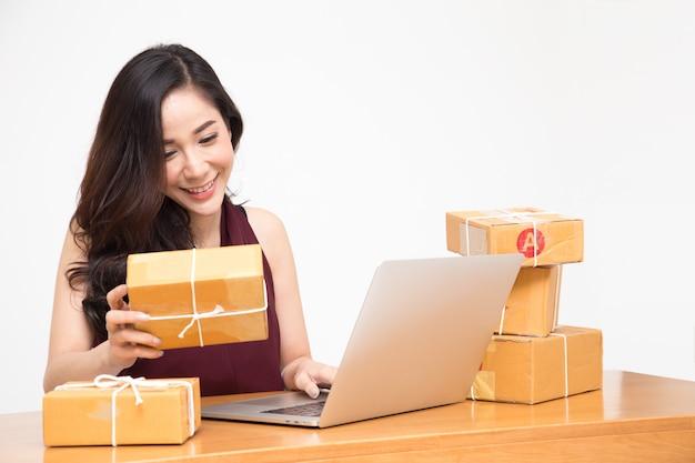 Junger asiatischer unternehmer, jugendlichon-line-geschäftseigentümer arbeiten zu hause, frauen, die produkt verpacken, das kundenauftrag von der website, geliefert als paket, service-paketzustellungs-reederei benutzen