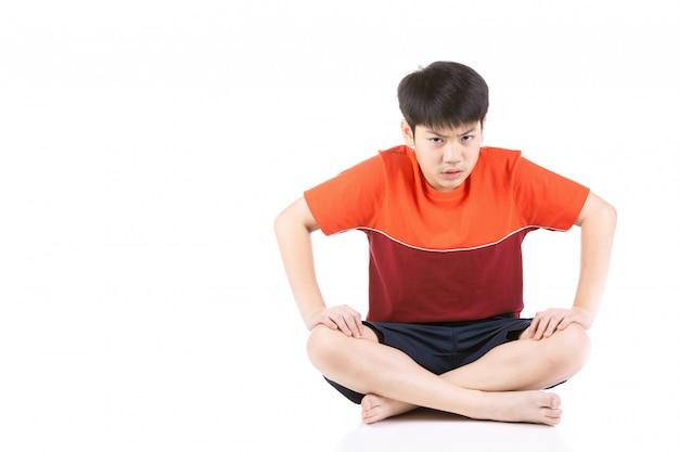 Junger asiatischer verärgerter junge des porträts, der über weißem hintergrund sitzt,