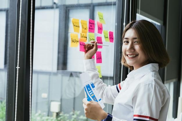 Junger asiatischer weiblicher kreativer entwickler der beweglichen anwendung, der bunte klebrige anmerkungen über die büroglaswand bearbeitet.