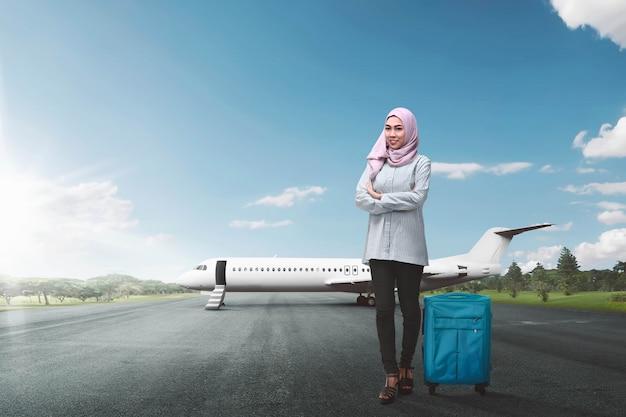 Junger asiatischer weiblicher moslem mit gehendem reisen des koffers