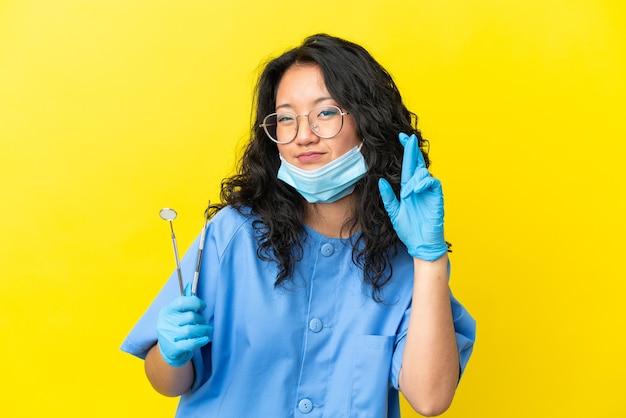Junger asiatischer zahnarzt, der werkzeuge über isoliertem hintergrund hält, mit gekreuzten fingern und das beste wünscht