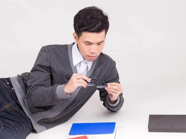 Junger asien-student im aufbaustudium mit zubehör des lernens.