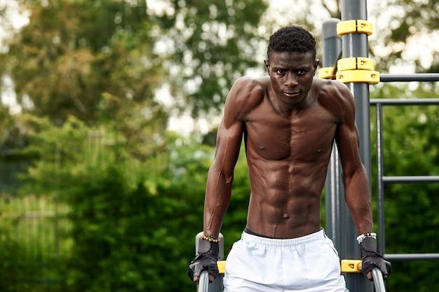 Junger athlet afroamericatsen, der am stufenbarren trainiert, ein athlet in hervorragender körperlicher verfassung, der übungen auf der straße auf dem spielplatz macht