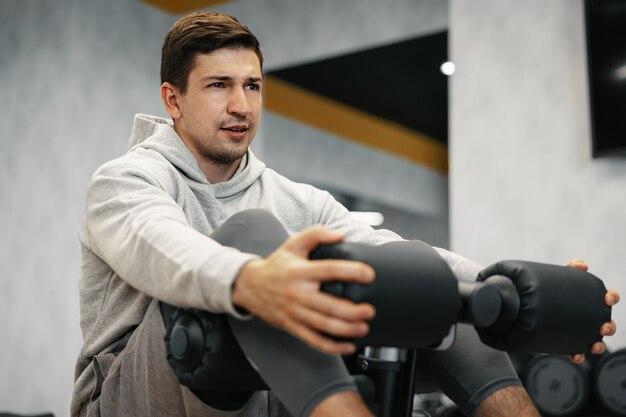 Junger athlet, der bauchmuskelübungen im modernen fitnessstudio macht