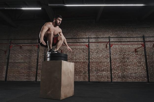Junger athlet, der boxsprung am crossfit-fitnessstudio tut. trainingsübungen. speicherplatz kopieren
