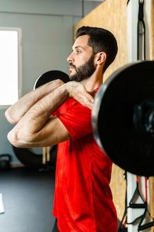 Junger athlet, der langhantel mit hanteln hebt, die im fitnessstudio trainieren