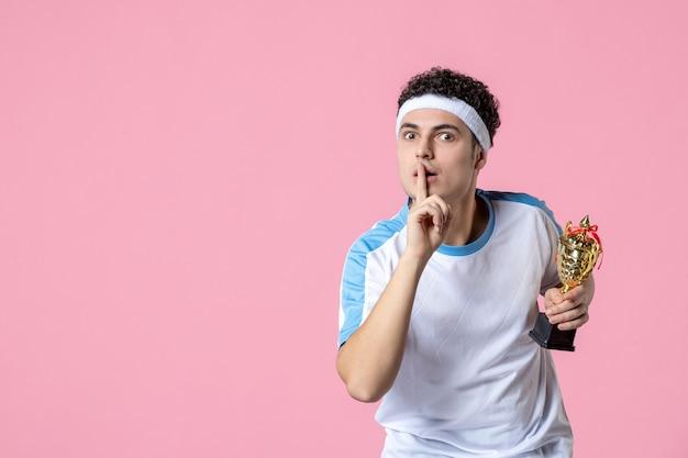 Junger athlet der vorderansicht in der sportkleidung, die goldenen becher hält