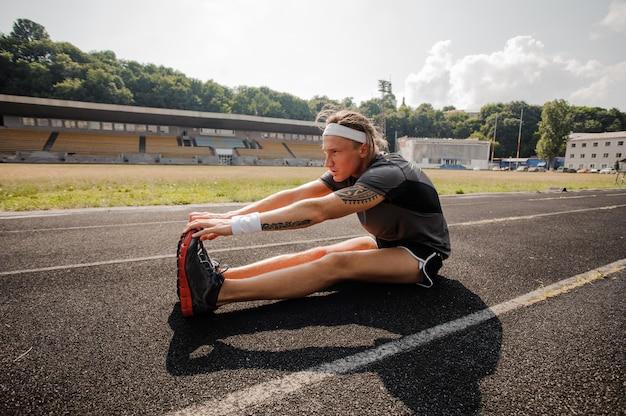 Junger athlet streckt sich auf der laufstrecke