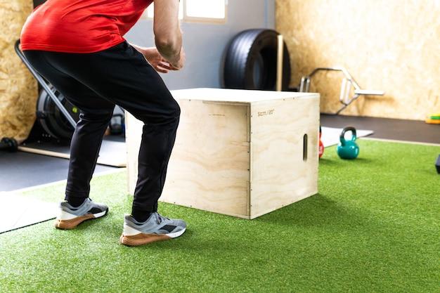 Junger athlet während der trainingseinheit, der im fitnessstudio in die box springt jump