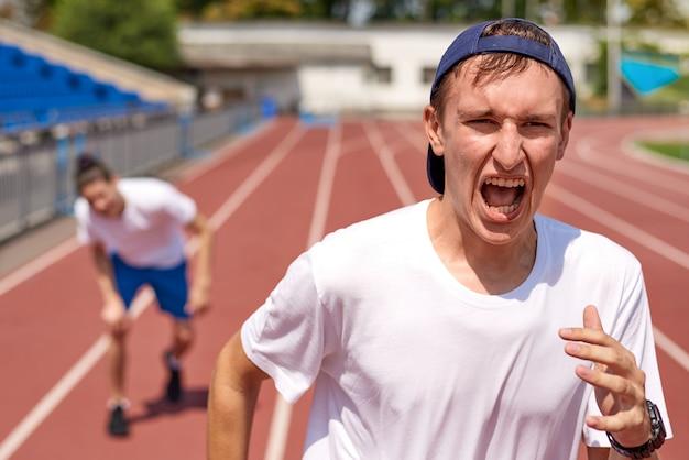 Junger athletenmann, der auf laufbahn mit dem gegner läuft