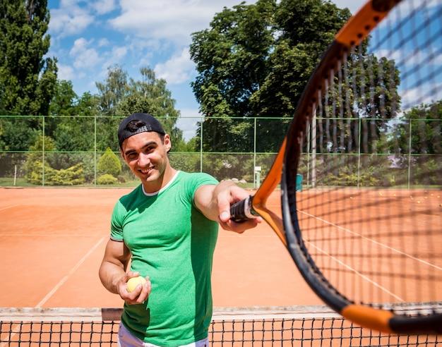 Junger athletischer mann auf tennisplatz