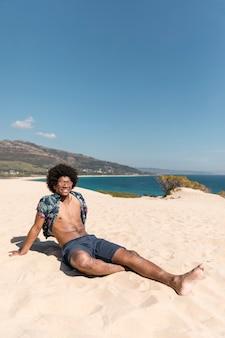 Junger athletischer mann, der auf sandigem strand sitzt