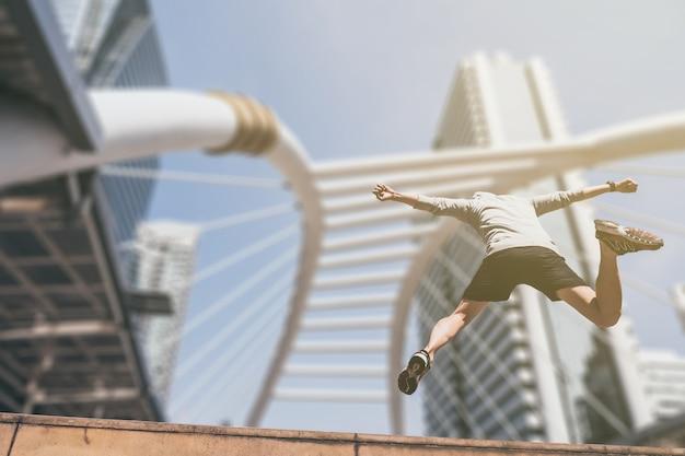 Junger athletischer mann, der beim trainieren auf stadtbrücke am morgen springt.