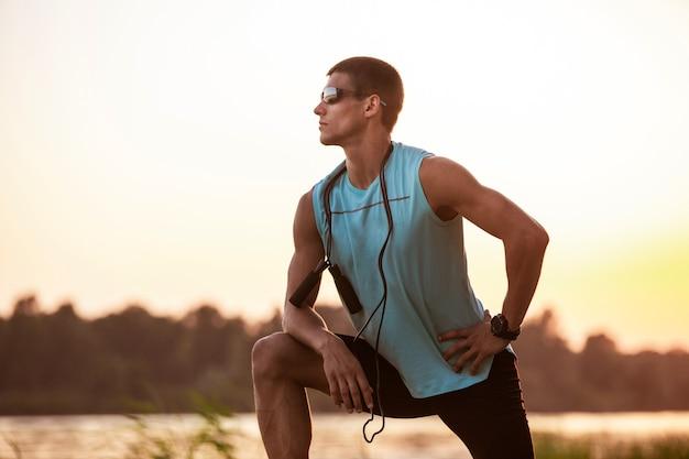 Junger athletischer mann, der draußen trainiert, am flussufer trainiert.
