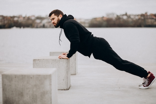 Junger athletischer mann, der durch den fluss trainiert und liegestütze tut