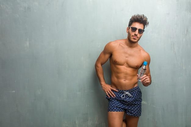 Junger athletischer mann, der einen badeanzug gegen eine schmutzwand nett und mit einem großen lächeln trägt,