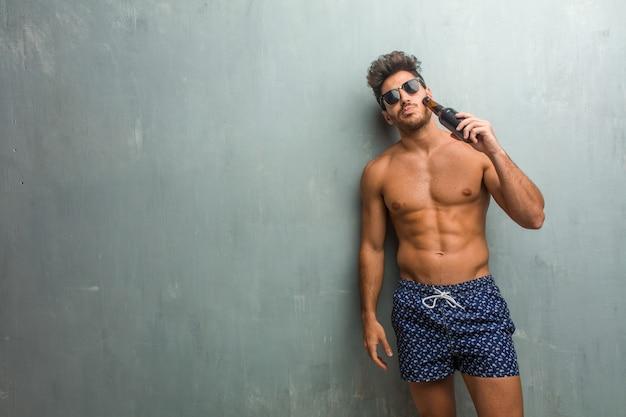 Junger athletischer mann, der einen badeanzug gegen eine schmutzwand trägt, verrückt und hoffnungslos, außer kontrolle schreiend, lustige verrückte freiheit ausdrückend und wild