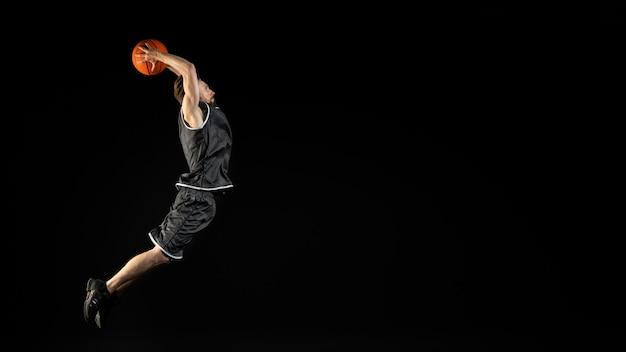 Junger athletischer mann, der einen basketball hält