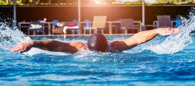 Junger athletischer mann, der im schwimmbad schwimmt