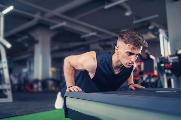 Junger athletischer mann, der liegestütze im fitnessstudio tut