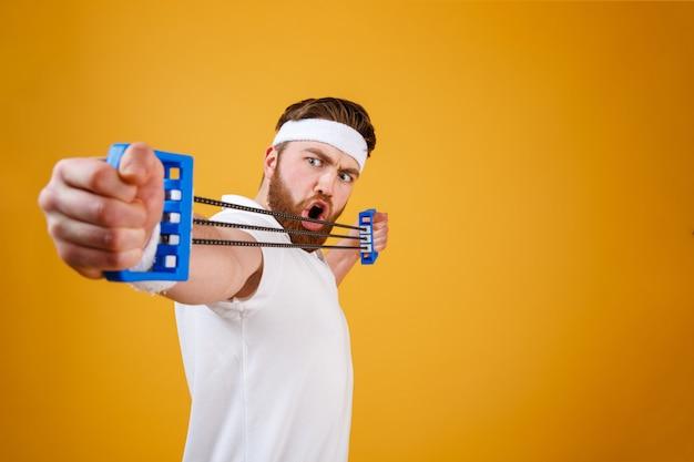 Junger athletischer mann, der mit brustvergrößerer oder widerstandsband ausübt