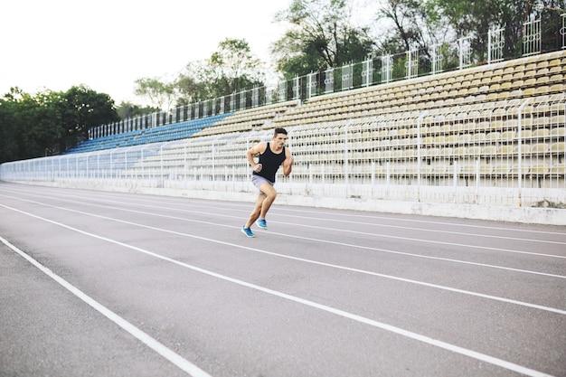 Junger athletischer mann, der morgens auf dem stadion läuft