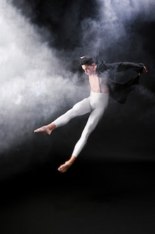 Junger athletischer mann, der nahe rauche gegen schwarzen hintergrund springt und tanzt