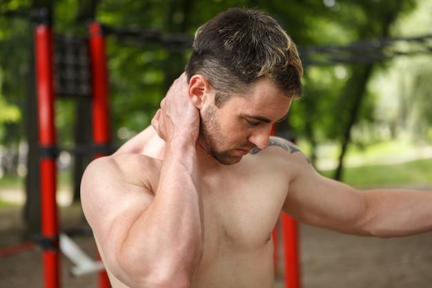 Junger athletischer mann, der unter nackenschmerzen leidet, schmerzende stelle massiert