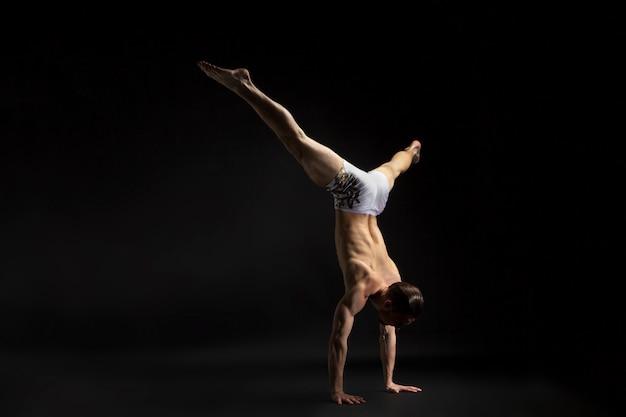 Junger athletischer mann, der zeitgenössisch über schwarzem hintergrund tanzt